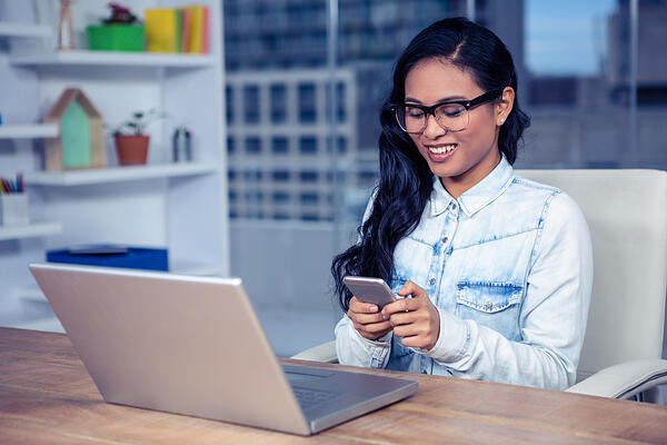 Smiling Asian woman with eyeglasses using smartphone in office
