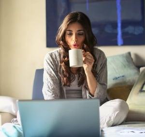 Woman using laptop drinking coffee