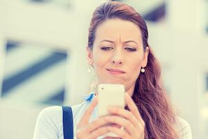 Closeup side profile portrait upset sad skeptical unhappy serious woman talking texting on phone displeased with conversation isolated city background. Negative human emotion face expression feeling